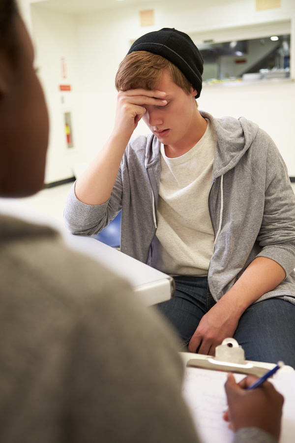 Young Man Talking To Counsellor Who Takes Notes